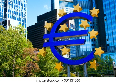FRANKFURT GERMANY - CIRCA MAY 6 2015: Symbol of Euro in front of European Central Bank in vivid and optimistic colours