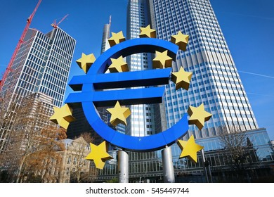 Frankfurt, Germany - december 29, 2013: Euro sign sculpture in a park among modern office towers in Frankfurt