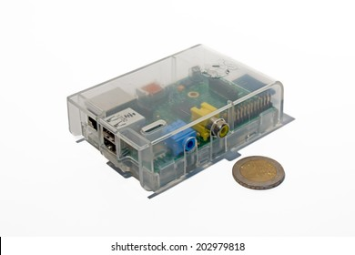 Frankfurt, Germany - June 16, 2014: Shot of a Raspberry Pi in transparent case on White with two Euro coin for Size comparism