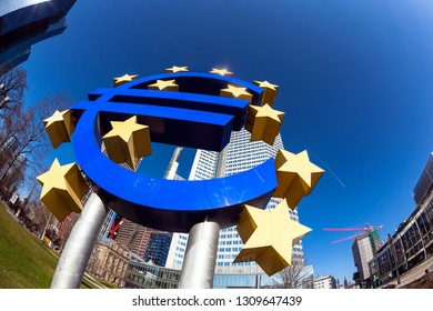 FRANKFURT, GERMANY - MAR 2, 2013: Famous euro sign in Frankfurt am Main under blue sky. At the background is the skyscraper of the european central Bank (ECB).