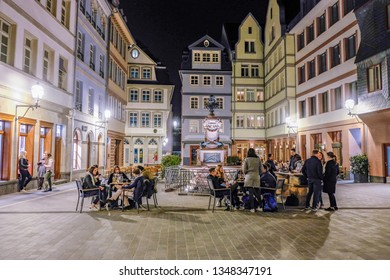 FRANKFURT, GERMANY - MAR 25, 2019: people enjoy a warm night in a restaurant at the new old town in Frankfurt.