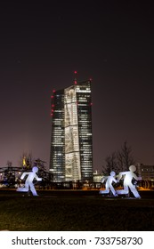 Frankfurt, Germany - March 13, 2016: The new ECB in Frankfurt at night during the luminale 2016 with an illuminated piece of art which should represent refugees (vertical)