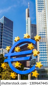 FRANKFURT, GERMANY - MAY 16, 2014: Famous euro sign in Frankfurt am Main under blue sky. At the background is the skyscraper of the european central Bank (ECB).