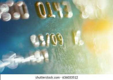 FRANKFURT, GERMANY - NOV 19, 2008: Abstract detail of credit card number embossed numbers with defocused surrounding numbers and yellow light flare sunbeam coming from right