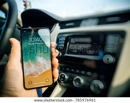 FRANKFURT, GERMANY - NOV 4, 2017: New gadge in male hand connecting his new iPhone X 10 to the navigation system of the car with CarPlay - message on GPS - new device detected