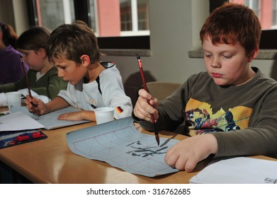 Frankfurt, Germany - November 11, 2014 - German pupils learning chinese calligraphy and origami with chinese exchange teacher