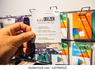 FRANKFURT, GERMANY - OCT 6, 2017: 50 Euro card in man hand point of view customer shopping for prepaid Deezer Music Gift card online money prepaid cards online music streaming