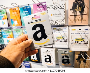 FRANKFURT, GERMANY - OCT 6, 2017: 50 Euro card in man hand point of view customer shopping for prepaid Amazon Gift card online money prepaid cards on shelf for online applications computer online