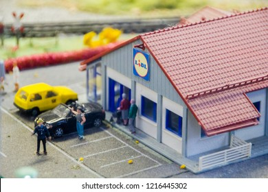 Frankfurt/ Germany - October 16 2018: Scenery with miniature houses of a LIDL supermarket chain store with people and cars on a parking area in front of it. Concept of grocery shopping
