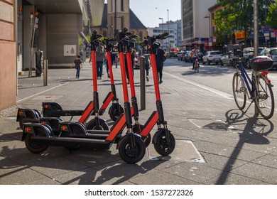 Frankfurt, Germany - OCTOBER 2019: Group of E-scooters from startup company with idea of Eco friendly mobility for urban lifestyle by sharing Electric Scooter, park on shady sidewalk in city.