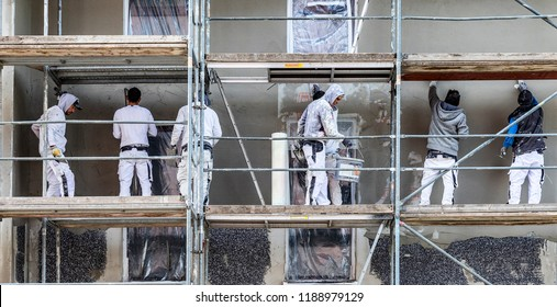 FRANKFURT, GERMANY - SEP 26, 2018:  painter and plasterer work on a scaffold to renovate an old wall. Most worker at construction site are from other contries in Germany.