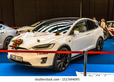 FRANKFURT, GERMANY - SEPT 2019: white wedding TESLA X with red roses electric car, IAA International Motor Show Auto Exhibtion.