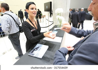 Frankfurt, Germany - September 13, 2011: Hostess giving a press kit to a specialized car journalist on IAA Frankfurt Motor Show on September 13, 2011 in Frankfurt.