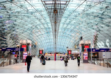FRANKFURT, GERMANY - SEPTEMBER 14, 2013: Passengers inside the beautiful glass structure of Frankfurt airport train staion.