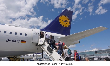 Frankfurt, Hesse / Germany - June 13, 2019: People boarding a Lufthansa commuter airplane for an inland flight via stairs