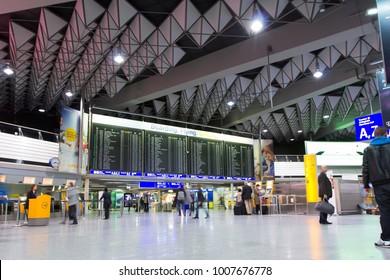Frankfurt International Airport (FRA), Frankfurt, Germany - 10.26.2016. Interior of the passenger terminal. Waiting hall, flights information board. Traveling passengers.