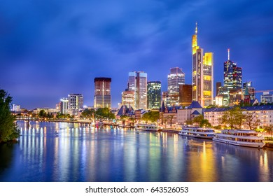 Frankfurt am Main city skyline at blue hour from the main river with traditional german buildings in front and modern skyscrapers behind