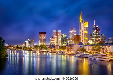 Frankfurt am Main city skyline at night from the main river with traditional german buildings in front and modern skyscrapers behind