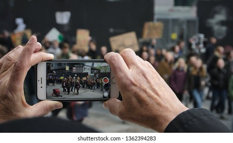 "Frankfurt am Main, Germany - April 5, 2019: ""Fridays for Future"" protest in Frankfurt. Onlooker filming Participants."