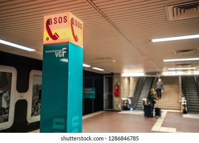 Frankfurt am Main, Germany - January 2019: blue colum in an underground public transport area with the red sign of SOS emergency call on top.