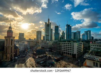 Frankfurt am Main, Germany - January 2019: City scraper and other buildings of the financial center, shot from above a mall, with sun and clouds in the background.