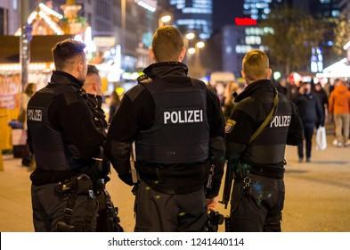 Frankfurt am Main, Germany - November 26 2018: German police officers at night in Christmas market in Frankfurt am Main.