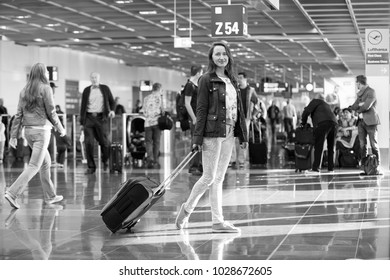 Frankfurt am Main, Germany - October 11, 2015: woman or pretty girl standing with black travel bag or suitcase on grey tile floor in airport with people. Traveling and baggage. Vacation and trip