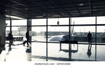 Frankfurt am Main, Germany - October 11, 2015: tourist passengers with suitcase, luggage in lounge hall. People wait for for flight in airport at big window glass. Wanderlust, vacation, travel.