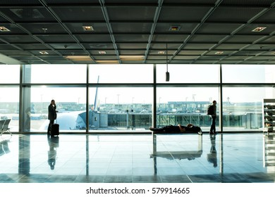 Frankfurt am Main, Germany-October 11, 2015: people or tourist passengers with suitcase and luggage waiting for flight in airport hall at big window glass