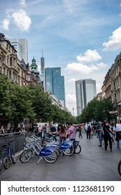 Frankfurt am Main,Germany-June 28,2018: A couple looks at two rental bikes in a pedestrian area with the Commerz Bank's headquarters in the background