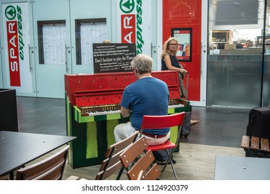 Frankfurt am Main,Germany-June 28,2018: A man plays the piano at Francfor-Main Central Station while waiting for his train