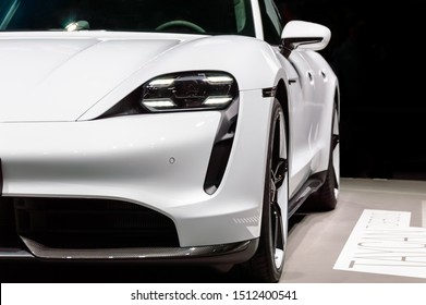 FRANKFURT - SEP 15, 2019: Close-up of white Porsche Taycan Turbo S: first fully electric Porsche sports car. Luxury supercar presented at IAA 2019 Frankfurt Motor Show. Front view with headlight