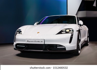FRANKFURT - SEP 15, 2019: White Porsche Taycan Turbo S is the first fully electric sports car from Porsche. Luxury supercar presented at IAA 2019 Frankfurt Motor Show. Front-side view