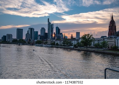 Frankfurt Skyline during the Sunset - Frankfurt am Main, Hessen, Germany at Night - a small boat drives along the main