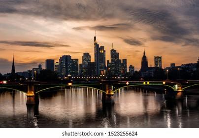 Frankfurt Skyline with Main river at sunset - orange hues