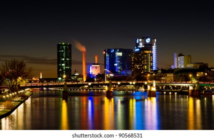 Frankfurt Westhafen skyline at night with power station reflecting in the Main river, Hessen, Germany