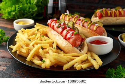frankfurter Sausage hotdogs with french potato fries, chips crinkle cut gherkins, ketchup and mustard. fast food