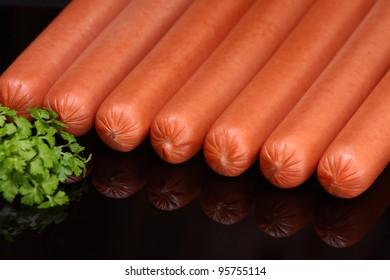 Frankfurter sausage on a dark background (raw hot dog)