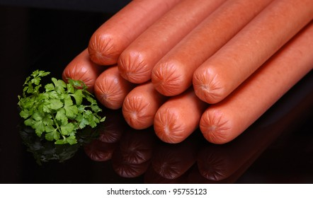 Frankfurter sausage on a dark background (raw hot dog)