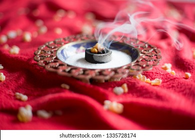 Frankincense burning on a hot coal. Frankincense is an aromatic resin, used for religious rites, incense and perfumes, incense smoke