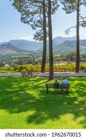 FRANSCHHOEK WESTERN CAPE SOUTH AFRICA - FEBRUARY 02.2020: A couple sitting on a banch and looking over the vinyards at Franschhoek, vertical