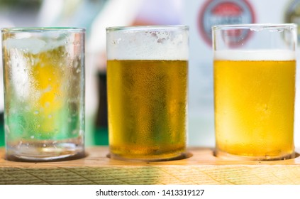 Franschhoek/South Africa - April 11, 2019: A photo of 3 glasses. Two is filled with beer and one is empty at a beer tasting restaurant.  Photo was taken at the Tuk Tuk microbrewery.