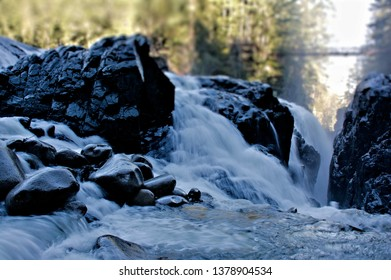 Frantic flow of water captured in a natural spectacle water gushing over the edges of the rock cliffs granite rocks and boulders downstream vanishing into a natural crevice with a steep fall