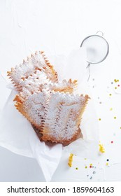 Frappe or chiacchiere Italian carnival fritters dusted with powdered sugar on  white wooden table. With free text space.