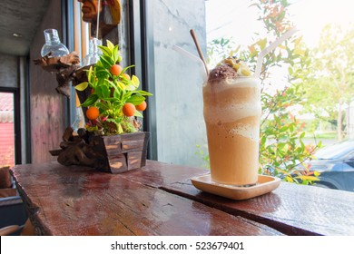 Frappuccino with caramel syrup and ice cream in a glass on wooden table