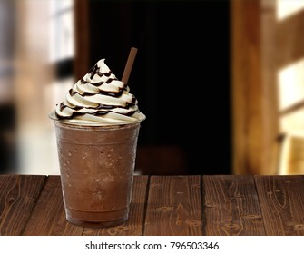 Frappuccino with chocolate sauce, syrup, sherbet in takeaway or to go cup on wooden table at cafe