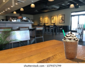 Frappuccino with cream and chocolate sauce on wooden table at cafe