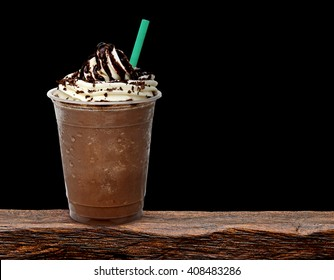 Frappuccino in take away cup on wooden table isolated on black