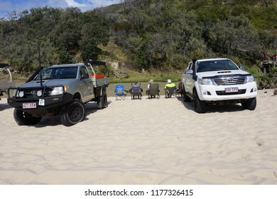 Fraser Island, Queensland, Australia, September 3, 2018. Big Cars dwarfing Men sitting in Camping Chairs along Eli Creek on 75 Mile Beach