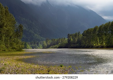 The Fraser River with rain clouds moving in over Mt. Cheam, Chilliwack, BC, Canada